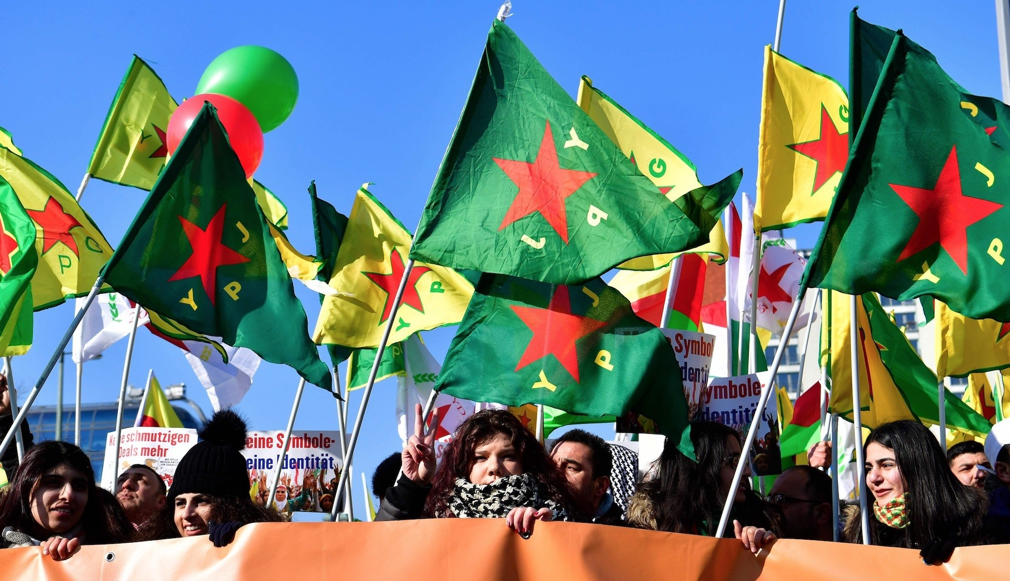 Protersters hold flags of the PKKu2019s Syrian affiliate, the Peopleu2019s Protection Units (YPG), and of its female branch, the Womenu2019s Protection Units (YPJ), during a demonstration in Berlin, Germany, on March 3.