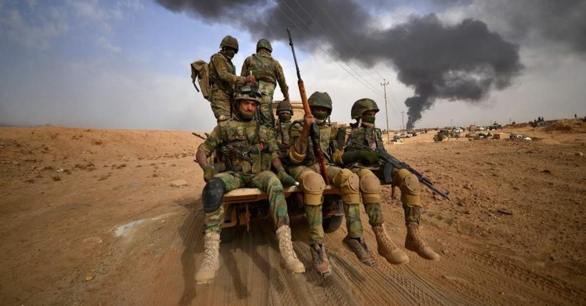 Members of the Popular Mobilization Forces (PMF) advance toward the city of Al-Qaim, Iraq, Nov. 3, 2017. (Reuters Photo)