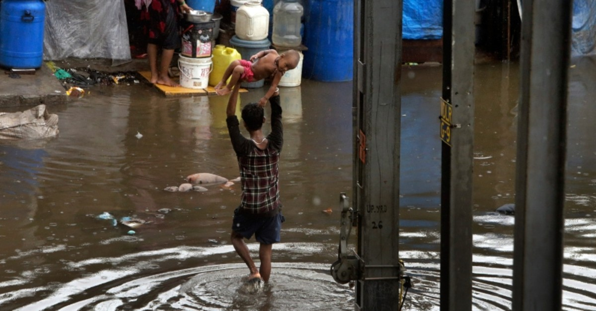 A man holds a child high above his head as he wades through a waterlogged street following heavy rains in Mumbai, India, Tuesday, July 2, 2019. (AP Photo)
