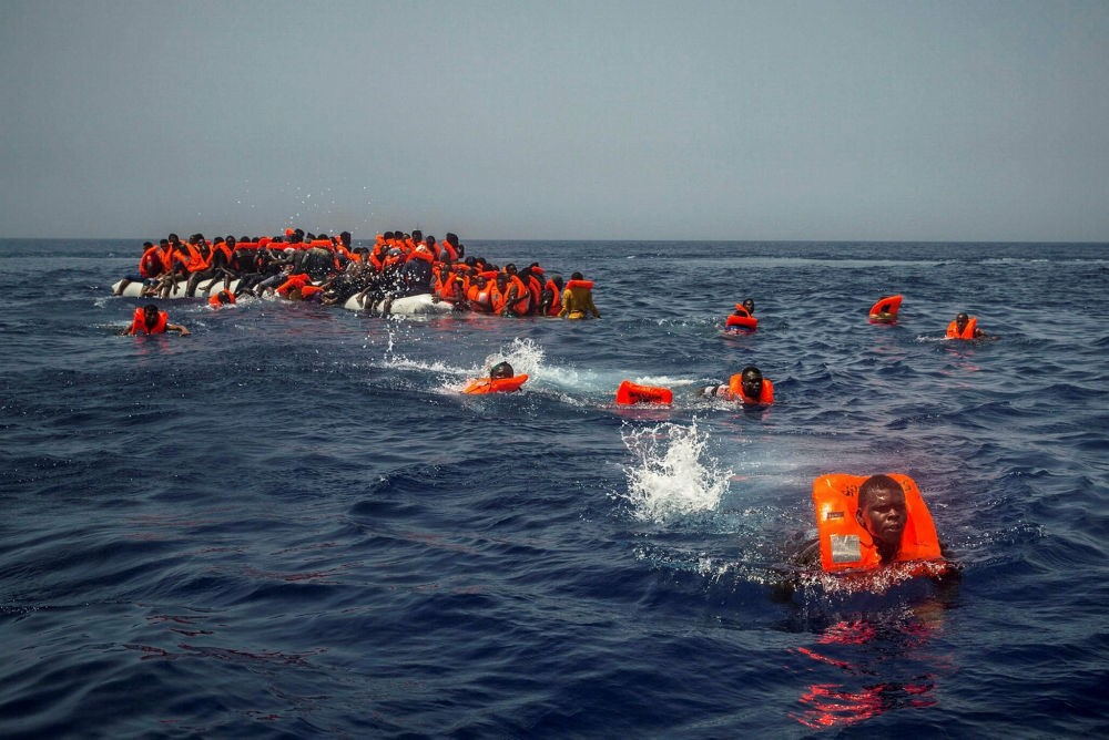 African migrants try to reach a Spanish NGO Proactiva open arms rescue ship from a punctured raft in the Mediterranean Sea, July 23, 2017.