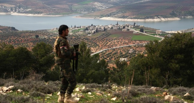 An FSA fighter walks along a ridge overlooking Lake Maydanki, north of the Syrian city of Afrin, after they took control of the nearby village of Ali Bazan from YPG terrorists on March 4.