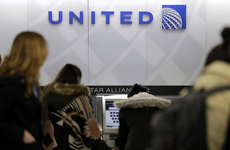 In this March 15, 2017, photo, people stand in line at a United Airlines counter at LaGuardia Airport in New York. (AP Photo)