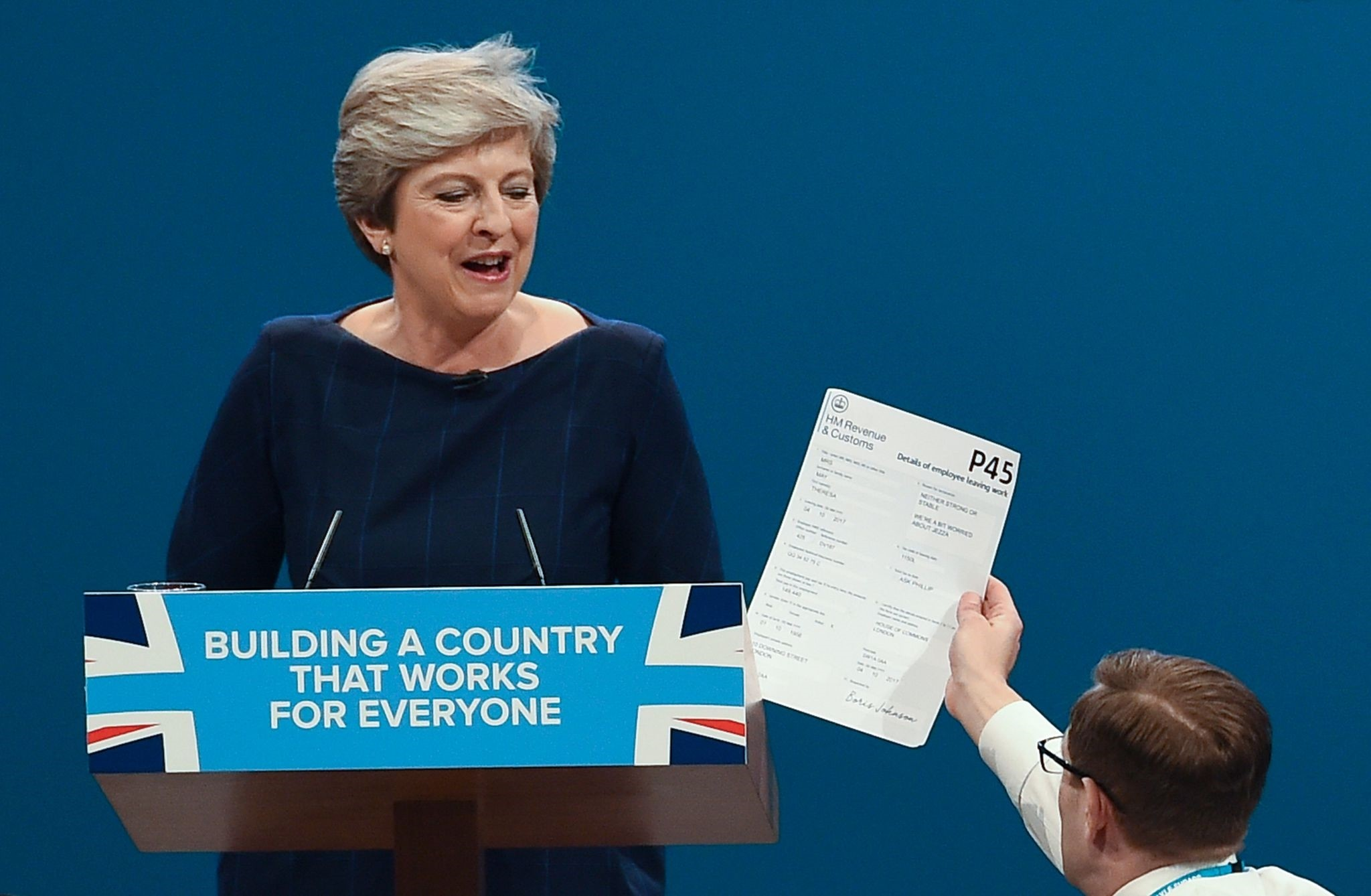 Protester comedian Simon Brodkin (R) gives a piece of paper written as a mock P45 (employee leaving form) to Britain's PM May on October 4, 2017. (AFP Photo)