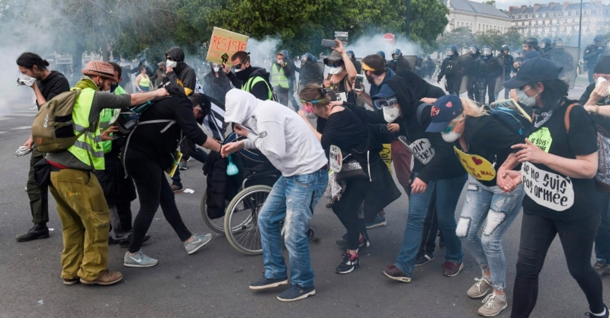 Protestors help a woman in a wheelchair while they try to protect themselves from tear gas during a demonstration called by the Yellow vest (Gilets jaunes) movement on May 11, 2019 in Nantes, western France (AFP Photo)