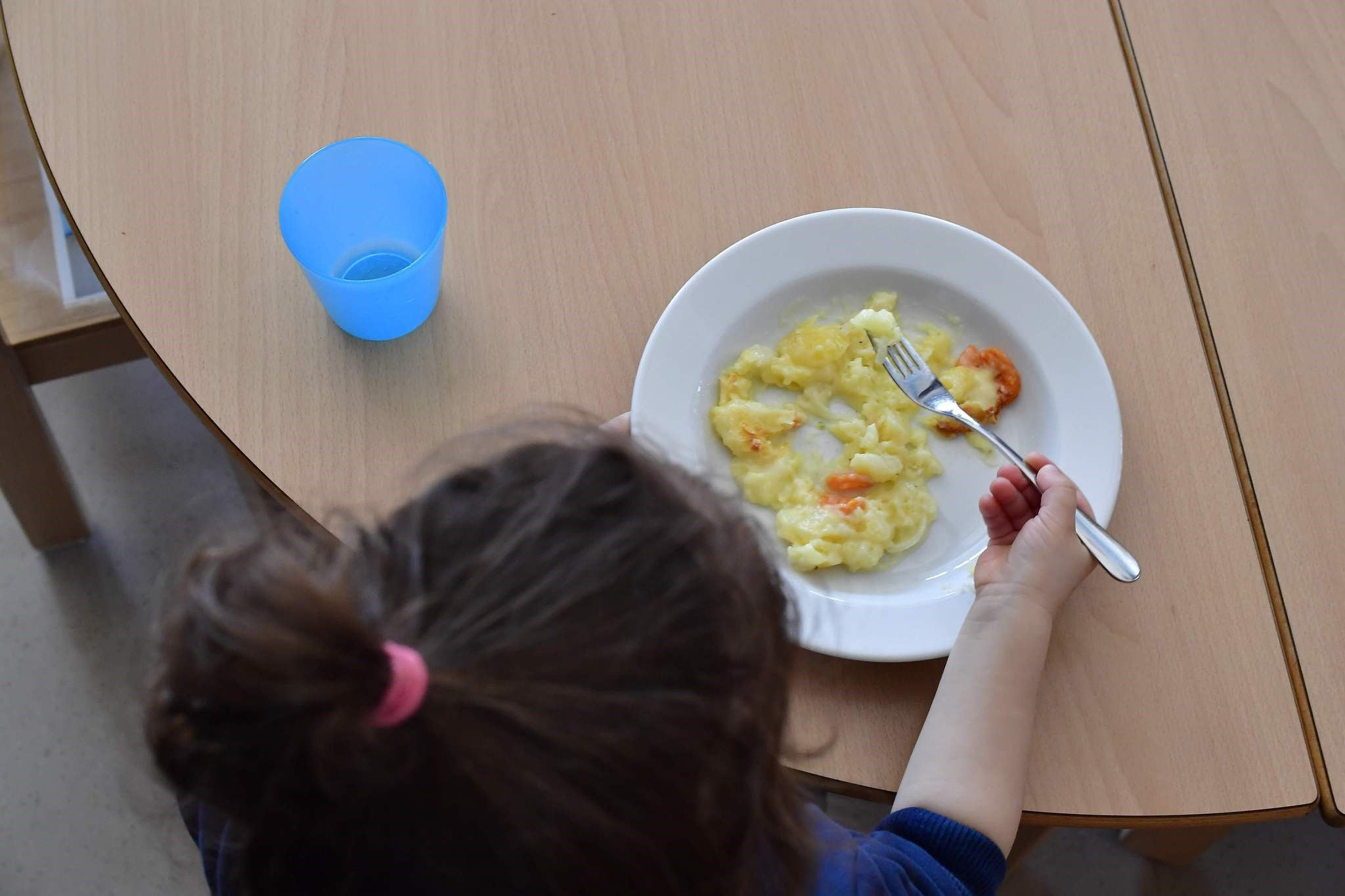 A girl eats lunch at a family center and kindergarden at the Gropiusstadt quarter, Berlin.