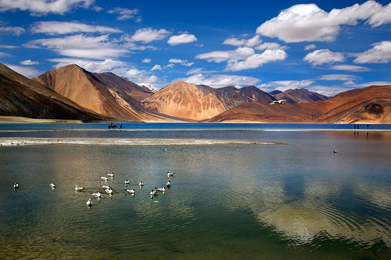 In this Sunday, June 17, 2016, photo, an Indian tourist rides on a horse back at the Pangong lake high up in Ladahak region of India. (AP Photo)