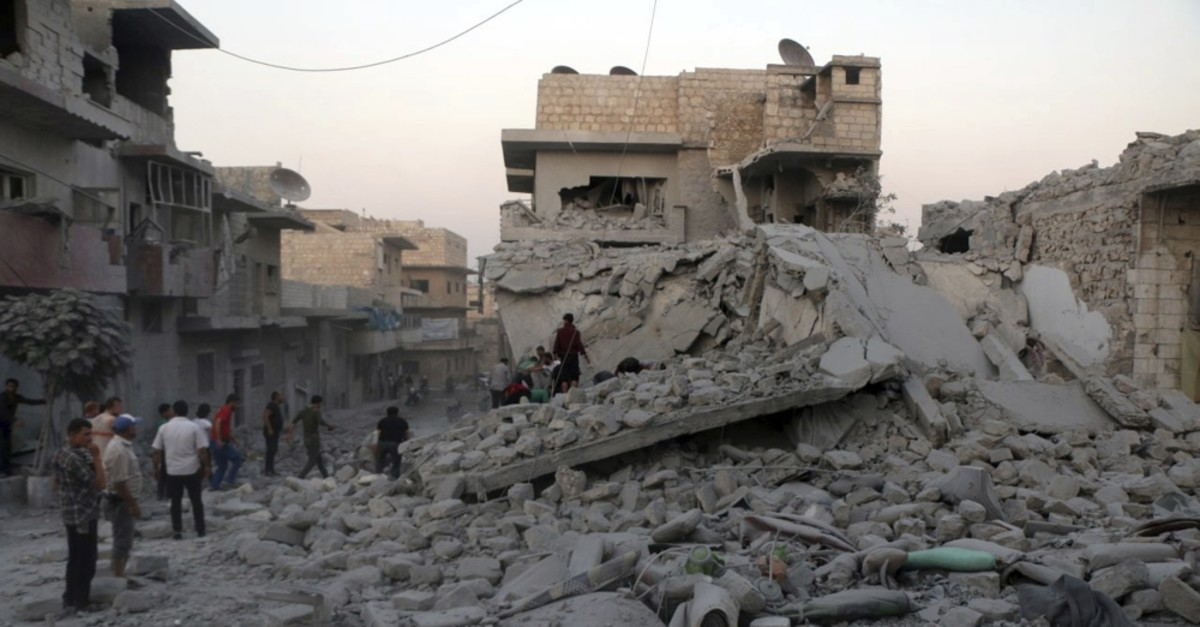 People searching for victims under the rubble of destroyed buildings hit by regime airstrikes in the northern town of Maaret al-Numan, Idlib province, Aug. 28, 2019.