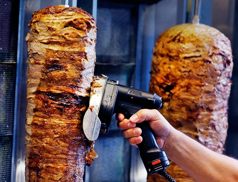 A man slices cuts of meat from a rotisserie du00f6ner spit inside a du00f6ner restaurant cafe in Frankfurt, Germany, Nov. 30, 2017.  (AP Photo)