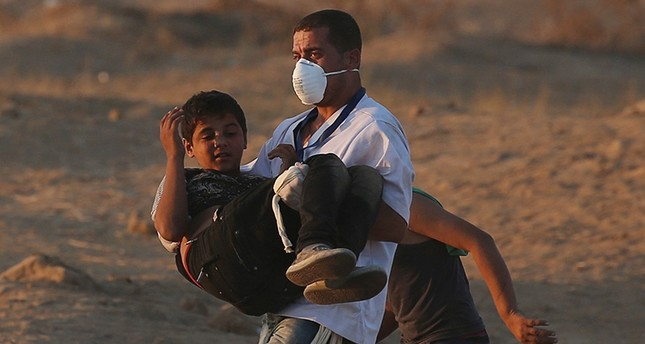 A wounded Palestinian boy is evacuted during a protest calling for lifting the Israeli blockade on Gaza and demanding the right to return to their homeland, at the Israel-Gaza border fence in the southern Gaza Strip Oct. 12, 2018. (Reuters Photo)