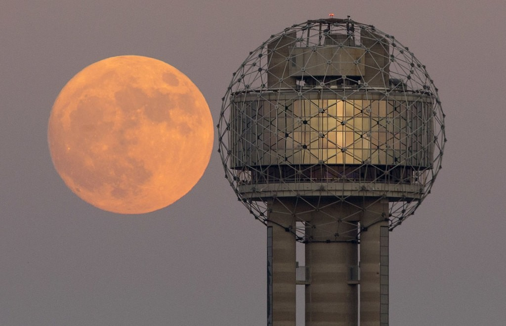 The moon rises behind Reunion Tower in downtown Dallas, Sunday evening, Nov. 13, 2016. AP Photo