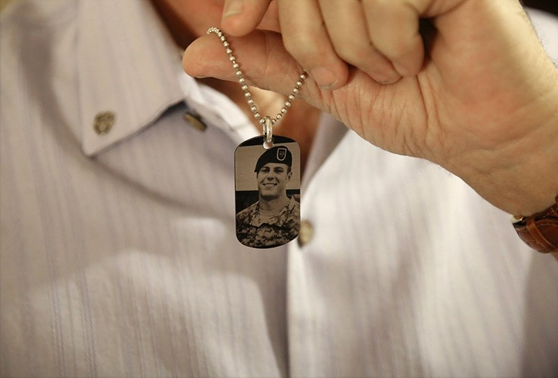 In this June 17, 2017 file photo, Brian McEnroe, the father of fallen U.S. Green Beret Kevin McEnroe, displays a memorial dog tag depicting his fallen son, in Amman, Jordan. (AP Photo)