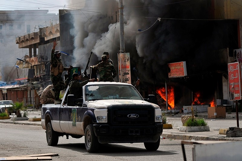 Members of Hashid Shaabi forces ride in a vehicle as smoke rises in shops at al-Qadisiya neighborhood, north of Tikrit April 3, 2015. (Reuters Photo)