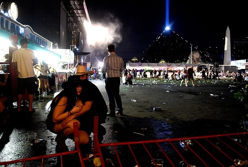 People take cover at the Route 91 Harvest country music festival after apparent gun fire was heard on October 1, 2017 in Las Vegas, Nevada (AFP Photo)