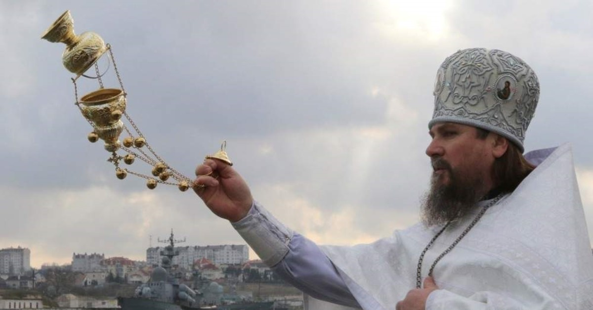 A priest conducts a service on the Karantinnaya Bay coast during celebrations of the Orthodox Christian feast of Epiphany, with Russian naval ships seen in the background, in Sevastopol, occupied Crimea, Ukraine, Jan. 19, 2019. (Reuters Photo)