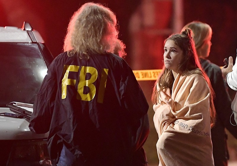 An FBI agent talks to a potential witness as they stand near the scene Thursday, Nov. 8, 2018, in Thousand Oaks, Calif. (AP Photo)