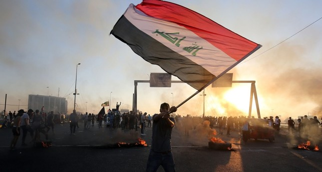 An Iraqi protester waves the national flag during a demonstration against state corruption, failing public services, and unemployment, in the Iraqi capital Baghdad on Oct. 5, 2019. (AFP Photo)