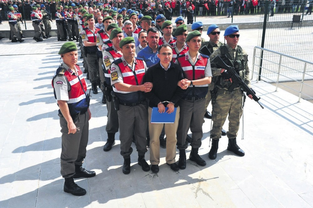 Officers accused of carrying out the putsch await for entrance to the courtroom in the company of soldiers escorting them in Ankara.