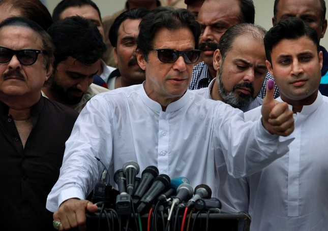 Pakistani politician Imran Khan, chief of Pakistan Tehreek-e-Insaf party, shows his marked thumb after casting his vote at a polling station for the parliamentary elections in Islamabad, Pakistan. (AP Photo)