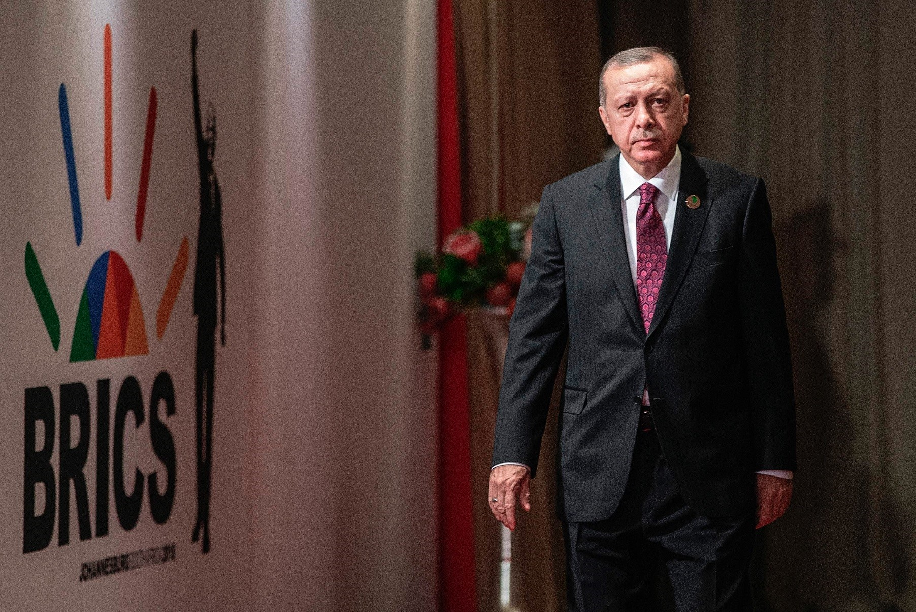 Turkeyu2019s President Recep Tayyip Erdou011fan arrives to attend a session meeting during the 10th BRICS summit
