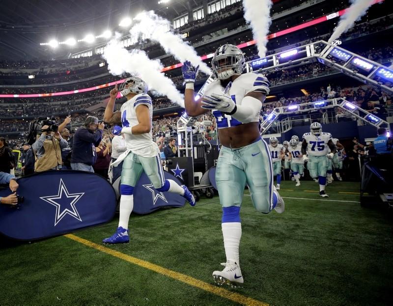 Dallas Cowboys running back Ezekiel Elliott (21) and quarterback Dak Prescott (4) run onto the field before a game against the Seattle Seahawks at AT&T Stadium in Arlington, Texas, U.S., Dec. 24, 2017. (Erich Schlegel-USA Today Sports via Reuters)