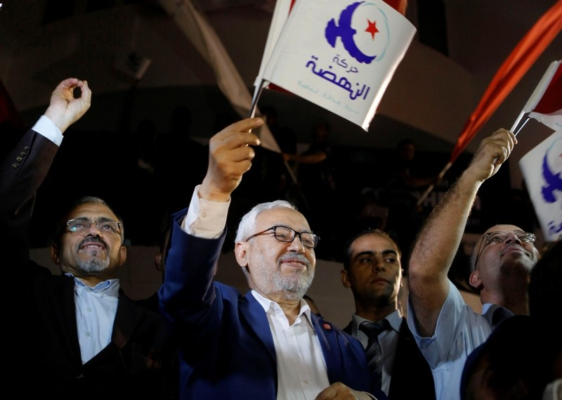 Rached Ghannouchi, leader of Ennahda, waves the party flag outside Ennahda's headquarters in Tunis October 27, 2014. (REUTERS Photo)