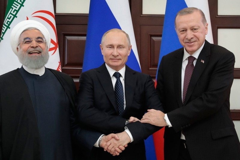 Russian President Putin, center, Iranian counterpart Rouhani, left, and President Erdogan shake hands while posing for a photo prior to the talks in the Bocharov Ruchei residence in Sochi, Russia, Thursday, Feb. 14, 2019. (AP Photo)