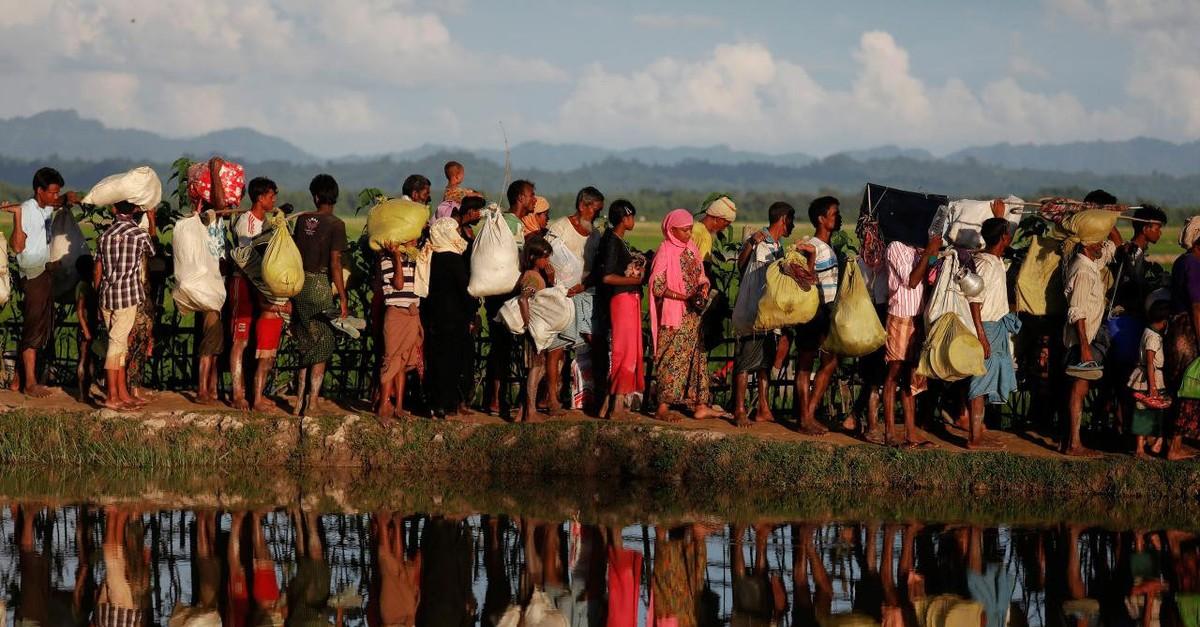 Rohingya refugees who fled Myanmar wait to be let through by Bangladeshi border guards after crossing the border in Palang Khali, Bangladesh, Oct. 9, 2017.