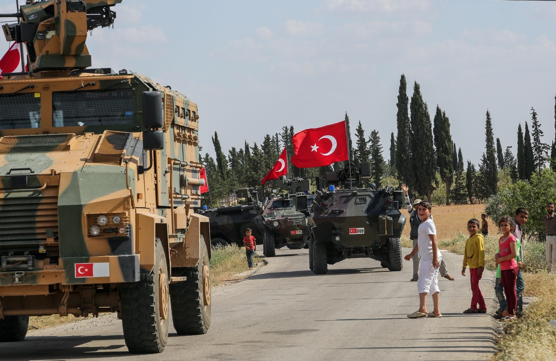 Turkish armored vehicles, welcomed by locals, on patrol in Manbij, June 22.