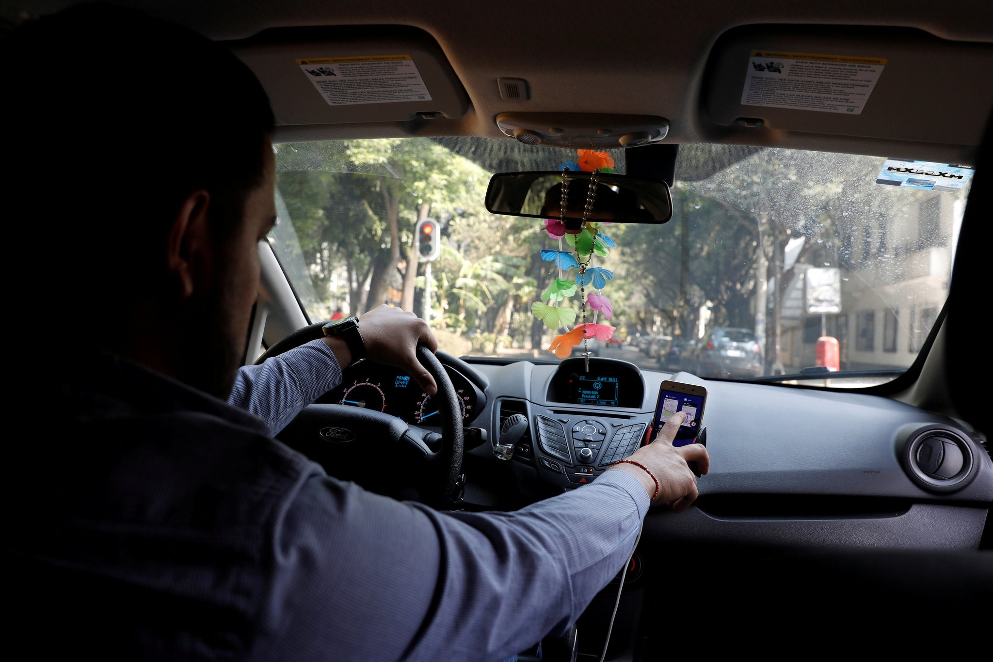 An Uber driver checks the route on a mobile phone inside his car in Mexico City, Mexico February 6, 2018. Picture taken on February 6, 2018. (REUTERS Photo)