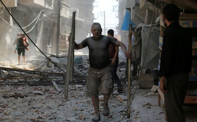 A Syrian man covered with dust carries pieces of metal on a street cluttered with rubble following an airstrike on the rebel-held neighborhood of Sakhur in Aleppo.