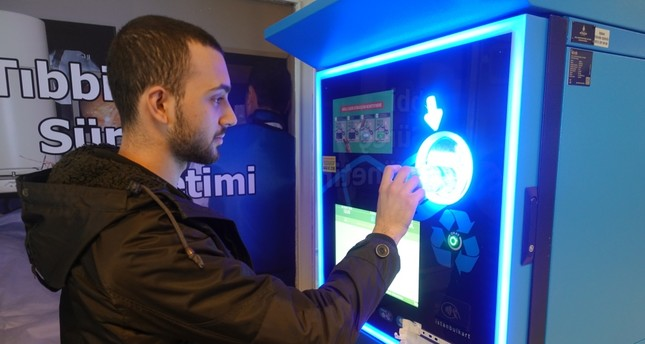 A man deposits a plastic bottle into Istanbul municipality's reverse vending machine, Feb. 28, 2019.