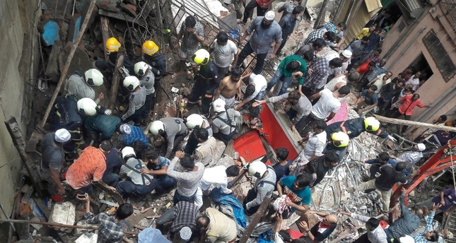 Rescue workers and residents search for survivors at the site of a collapsed building in Mumbai, India, July 16, 2019. (Reuters/Stringer)