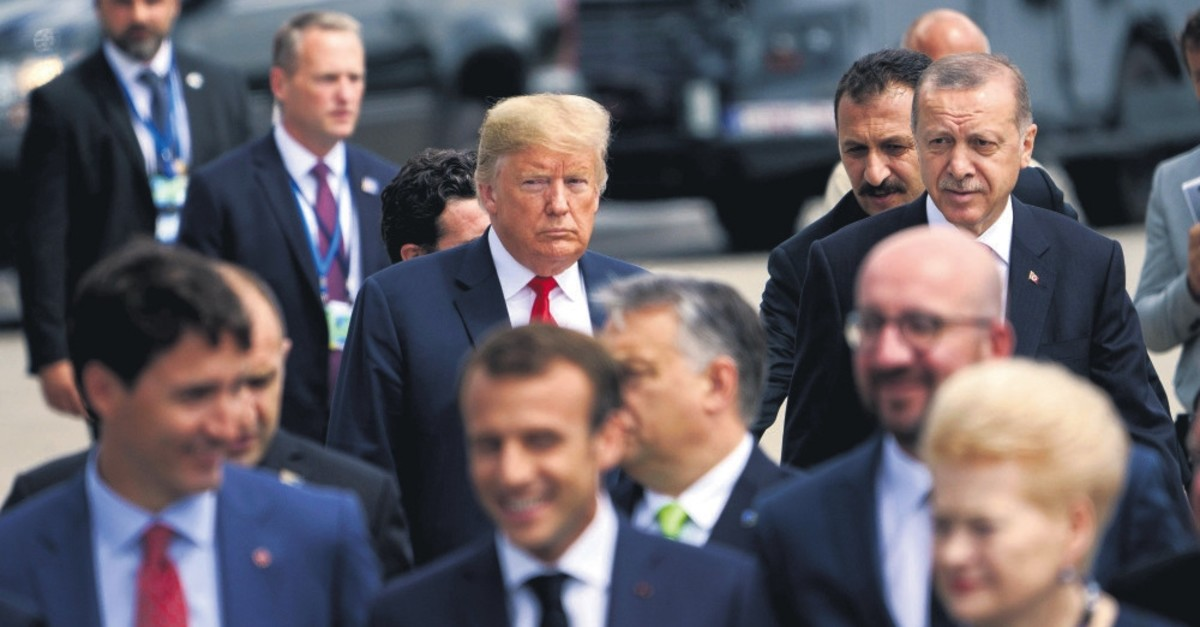 U.S. President Donald Trump (L) and President Recep Tayyip Erdou011fan follow other leaders to a family photo during the NATO summit at Brussels, July 11, 2018.