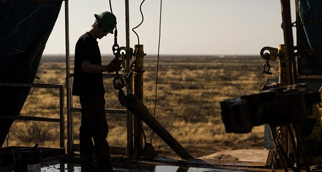A worker waits to connect a drill bit on Endeavor Energy Resources LP's Big Dog Drilling Rig 22 in the Permian basin outside of Midland, Texas, U.S., on Friday, Dec. 12, 2014. (Bloomberg Photo)