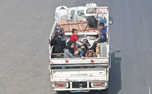 Residents of Idlib province flee toward the Syrian Turkish border, Sept. 10.
