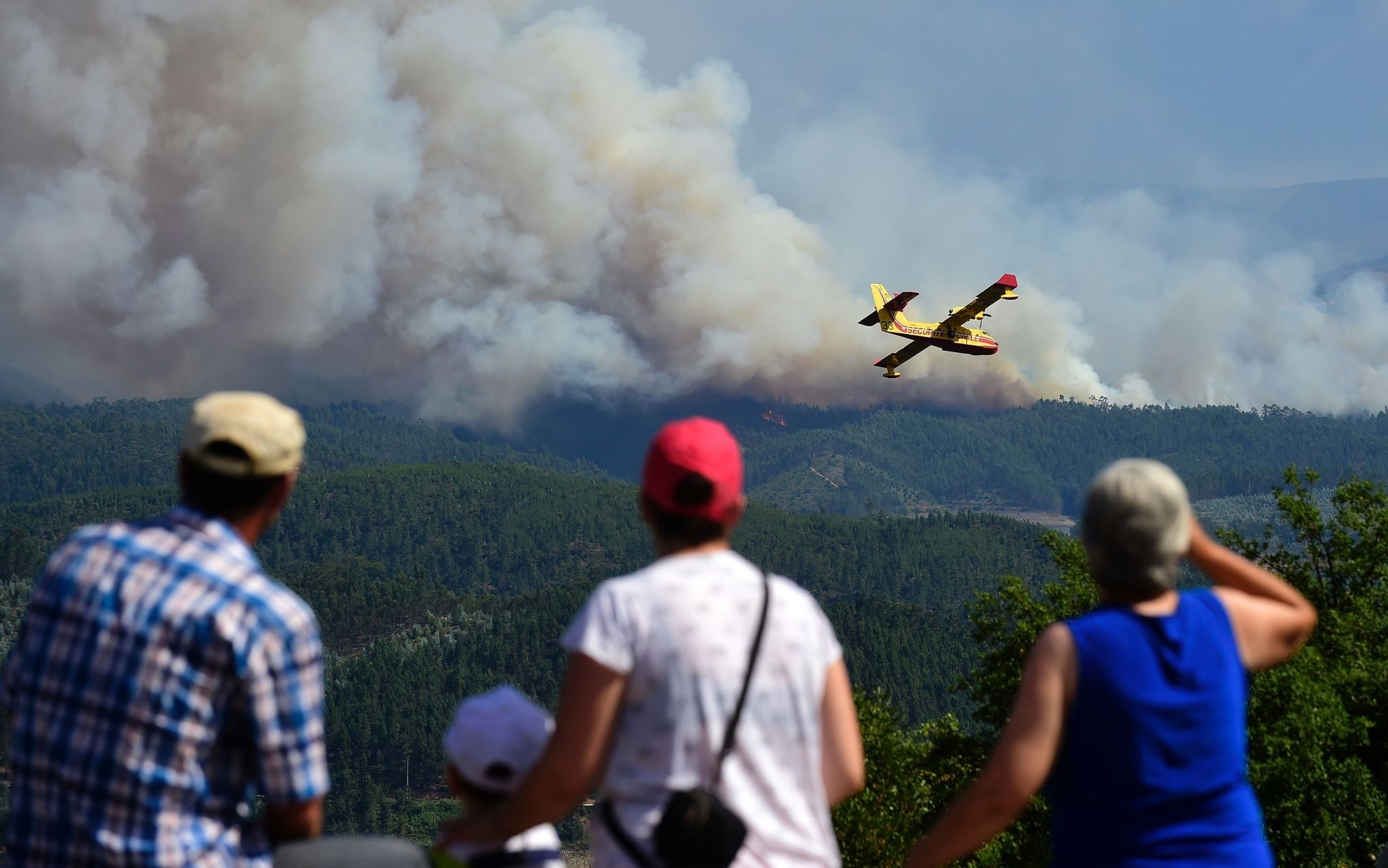 Some locals watch a Canadair plane overflying smoke columns taht raise as wildfires burn close to Pedrogao Pequeno, on June 20, 2017 (AFP Photo)