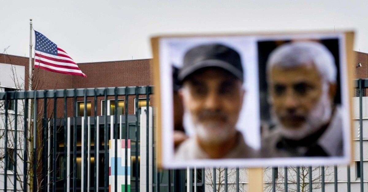 A picture shows the US flag and portraits of Iranian commander Qasem Soleimani (L) and Iraq's Hashed al-Shaabi military network deputy chief Abu Mahdi al-Muhandis, both killed  in Baghdad early on January 3, 2020 (AFP Photo)