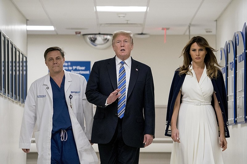 President Donald Trump, center, accompanied by and first lady Melania Trump, right, and Dr. Igor Nichiporenko, left, speak to reporters while visiting with medical staff at Broward Health North in Pompano Beach, Fla. (AP Photo)