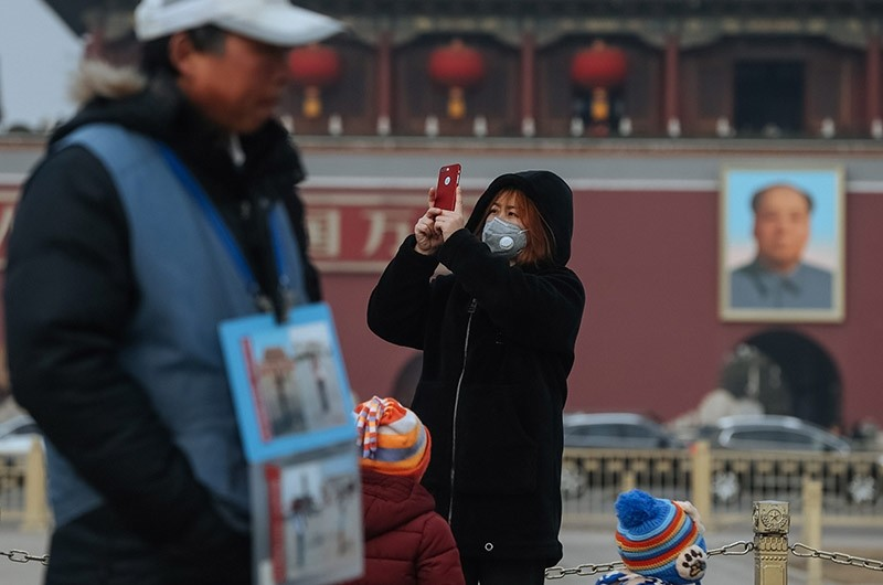 A visitor wearing a protective mask takes a photo at Tiananmen Square in Beijing, China on Jan. 27, 2017. (EPA Photo)