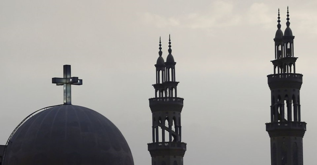 A cross above a church is seen alongside minarets of a mosque April 17 in Cairo (Reuters File Photo)
