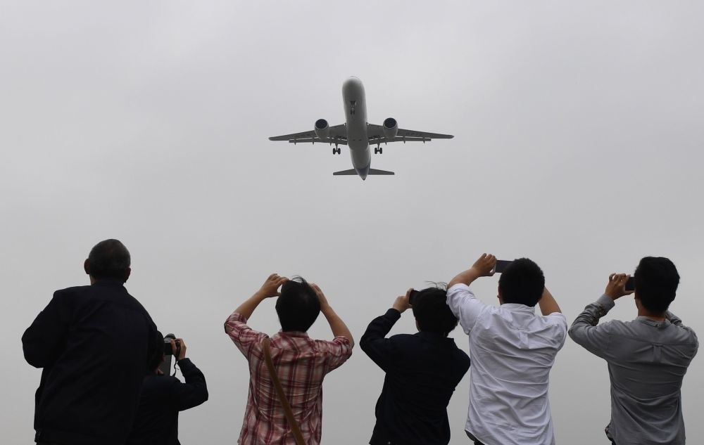 Spectators take photos as they watch the Comac C919.