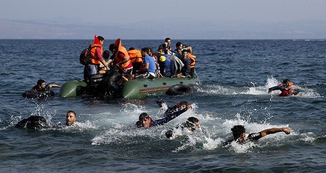 Refugees whose boat stalled at sea while crossing from Turkey to Greece swim to approach the shore of the island of Lesbos, Greece, on Sunday, Sept. 20, 2015.