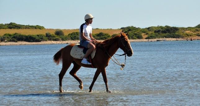 A tourist enjoys a horseback safari in Aydın's resort town of Didim.