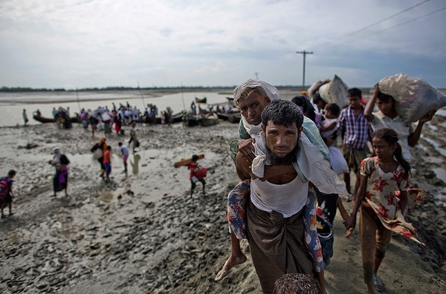 A Rohingya Muslim man from Myanmar carries an elderly woman after they crossed the border into Bangladesh from Myanmar, in Teknaf, Bangladesh, Friday, Sept. 29, 2017. (AP Photo)