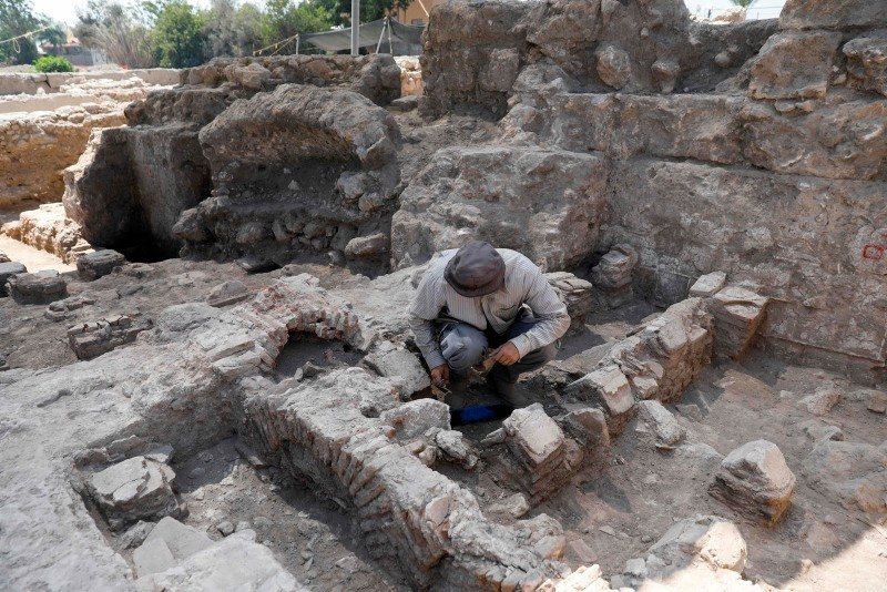 An Israel Antiquities Authority archeologist checks a bathing place at a site from Byzantine time found during a large excavation in the central Israeli town of Gedera near the ancient archeological site of Tel Qatra on July 31 2018. (AFP Photo)