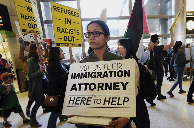 A woman offers legal services at the customs arrival area as demonstrators opposed to President Donald Trump's executive orders barring entry to the U.S. (AP Photo)