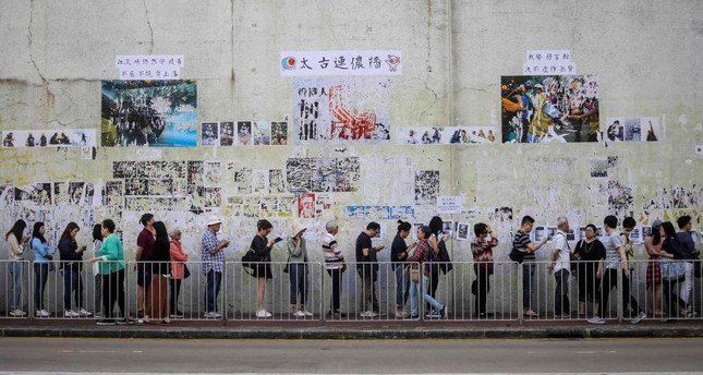 People queue to cast their vote in front of a Lennon Wall adorned with tattered posters in support of the ongoing protests, during the district council elections in Tai Koo in  Hong Kong on November 24, 2019. (AFP Photo)