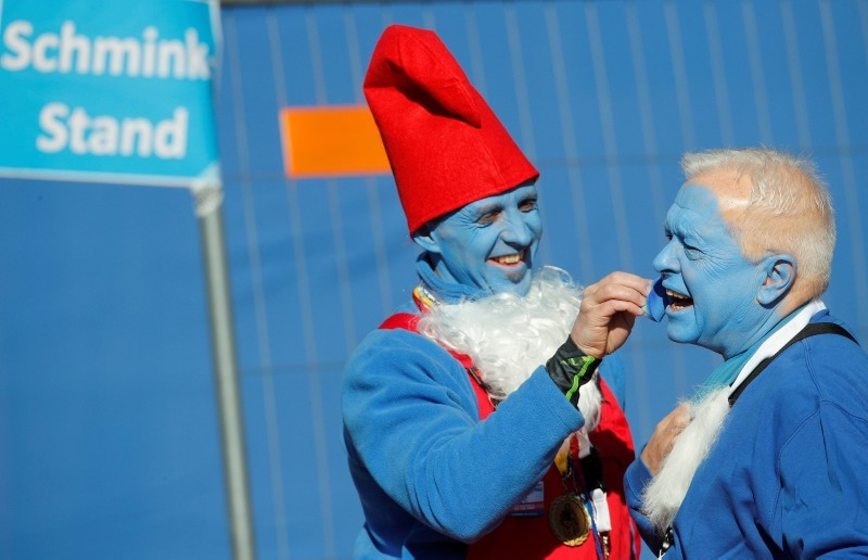 A participant dressed as a smurf paints a man's face blue before an attempt to hold the world's largest meeting of smurfs (Reuters Photo)