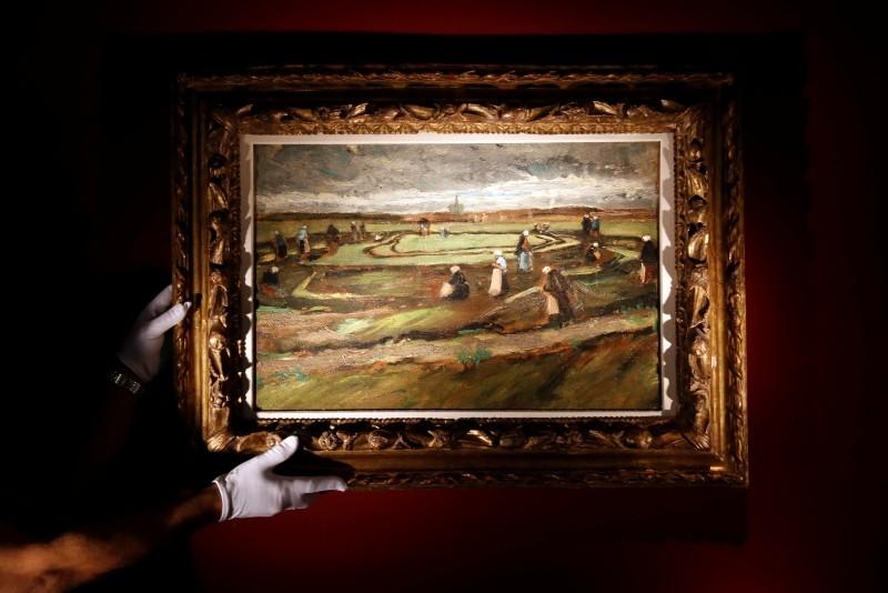 A staff presents a painting entitled 'Raccommodeuses de Filets dans les Dunes' (Women Mending Nets in the Dunes) by Dutch artist Vincent Van Gogh at the Artcurial headquarter in Paris (EPA Photo)