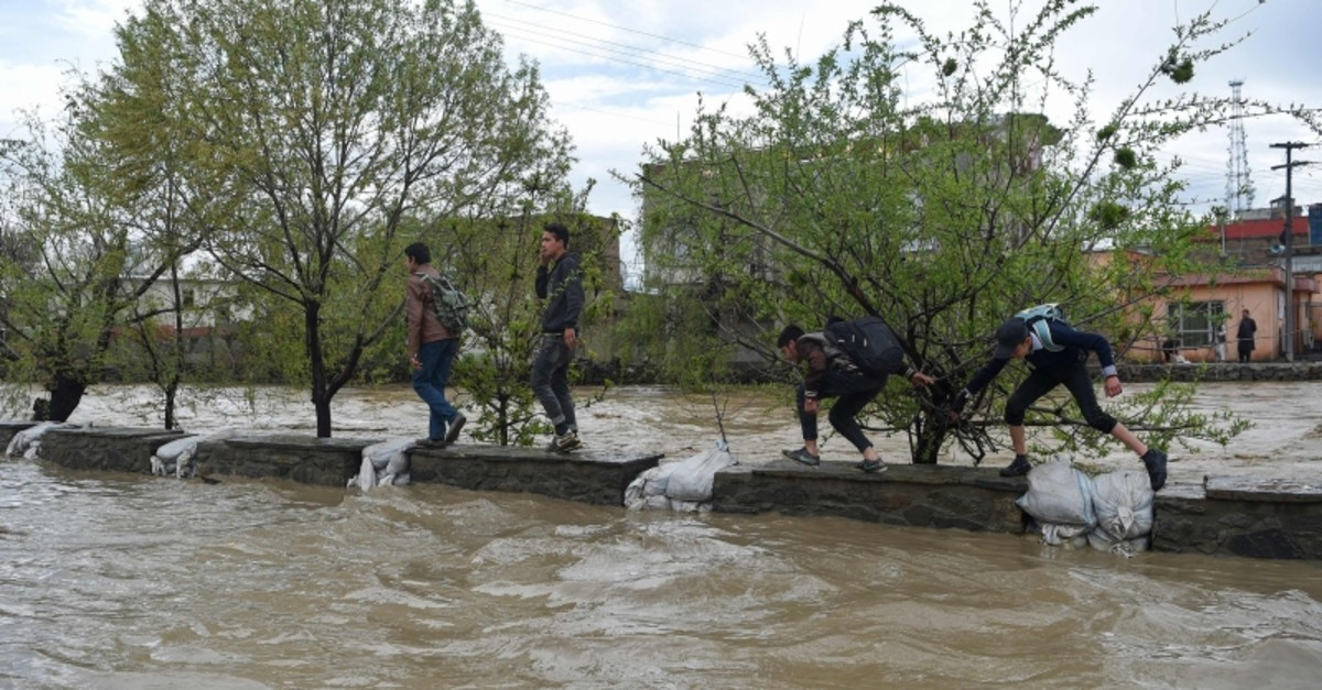 Afghan youths walk after heavy rain falls along the Kabul river in Kabul on April 16, 2019. (AFP Photo)